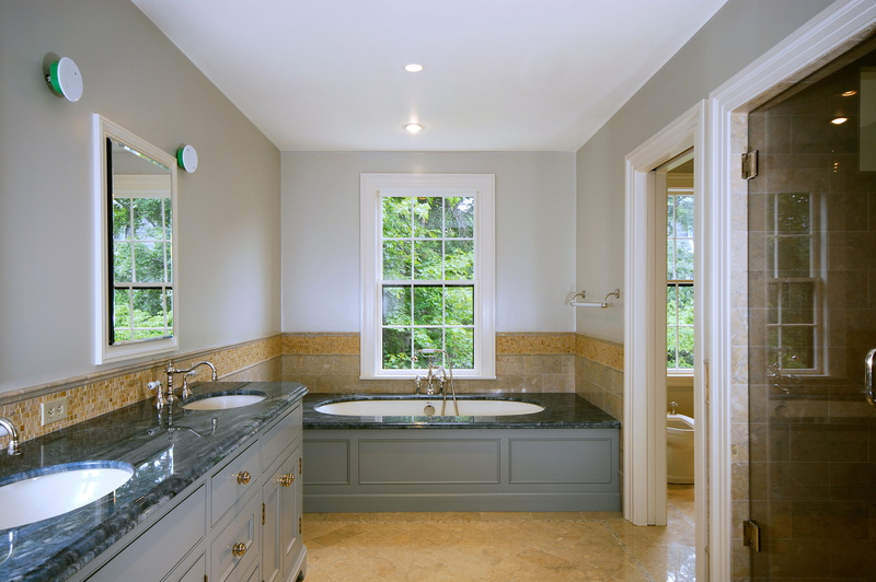 Remodeled bathroom with double sinks and large tub