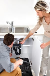 Woman with a plumber looking under the kitchen sink